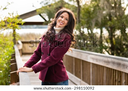 Happy young woman dressed for cold weather on nature walk near river - stock photo