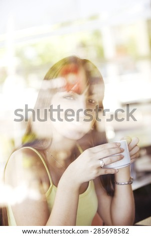 Happy young woman drinking coffee - stock photo