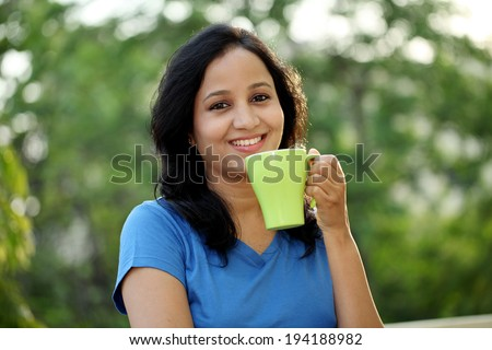 Happy young woman drinking coffee at outdoors - stock photo