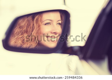 Happy young woman driver reflection in car side view mirror. Positive human face expressions, emotions. Safe winter trip, journey driving concept - stock photo