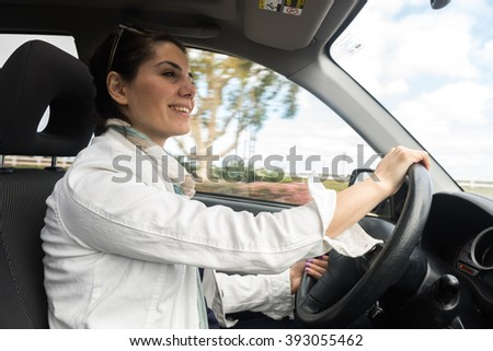 Happy young woman driving a car with a motion blured background