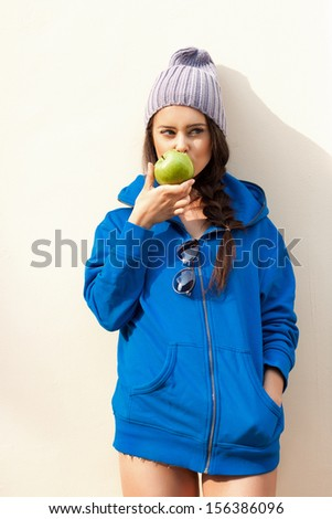 Happy Young Woman Eating Apple near yellow Wall and looking at camera. Diet. Dieting concept. Healthy food. Outdoors - stock photo