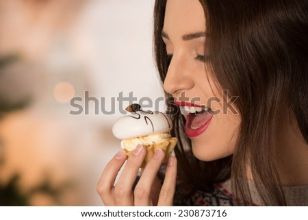 Happy young woman eating candy near christmas tree - stock photo