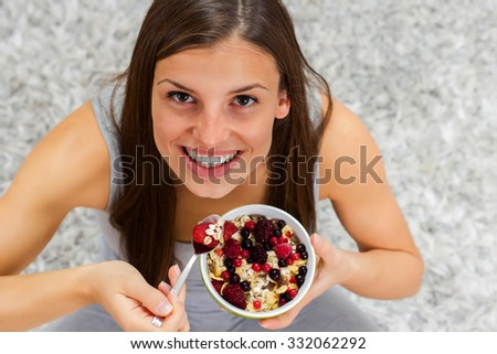 Happy young woman eating cereal muesli with fruits in bowl at home. Healthy Food and Dieting concept. - stock photo