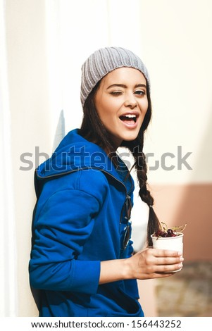 Happy Young Woman Eating Cherry and winking. Dieting concept. Healthy food. Outdoors - stock photo