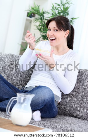 Happy young woman eating cornflakes at home - stock photo