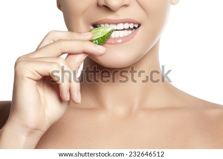 Happy young woman eating cucumber. A close-up of beautiful girl eating cucumber. Healthy smile with white teeth. Vegetarian menu - stock photo