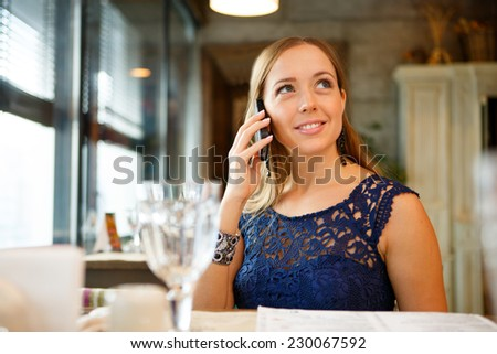 Happy young woman eating sushi in a restaurant and using mobile phone - stock photo