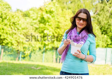 Happy young woman eating thai food from go-away box