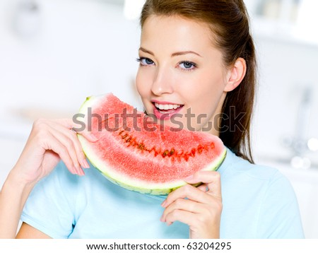 happy young woman eats a red  watermelon