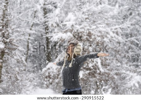 Happy young woman embracing beautiful life with her arms wide open as she is standing outside in a snowy winter woodland with snowflakes falling. - stock photo