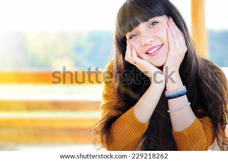 Happy young woman enjoying autumn weather outdoors. copyspace