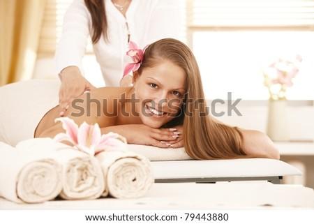 Happy young woman enjoying back massage, looking at camera, smiling. - stock photo
