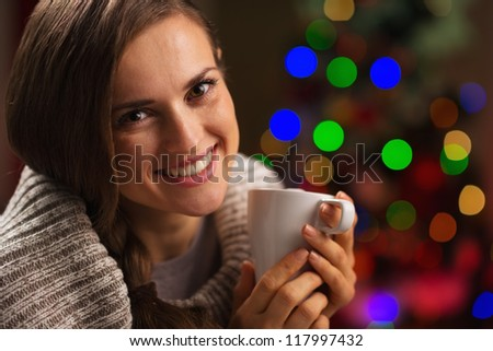 Happy young woman enjoying cup of hot chocolate in front of Christmas lights - stock photo