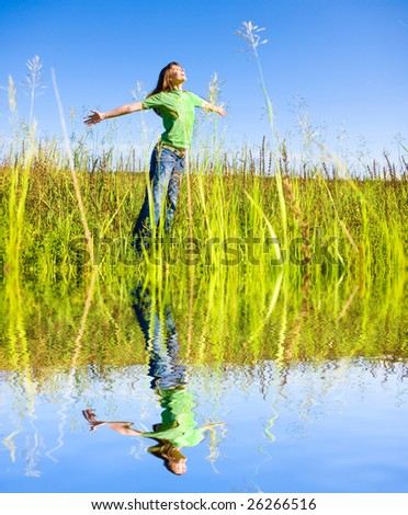 Happy young woman enjoying summer. Against the backdrop of blue sky. - stock photo