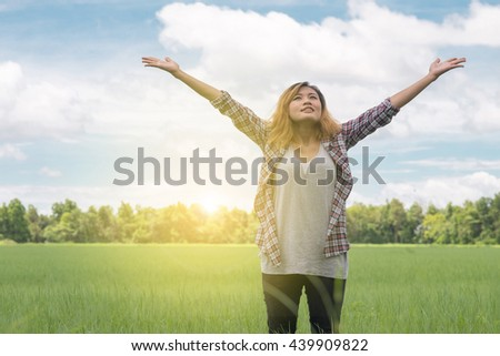 Happy young woman enjoying sunny day on green meadow background. blue sky.