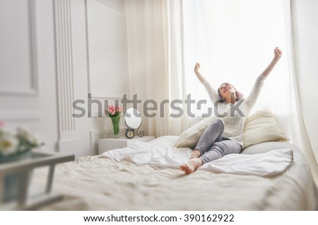 Happy young woman enjoying sunny morning on the bed  - stock photo