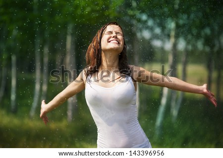 Happy young woman enjoying the rain in summer - stock photo