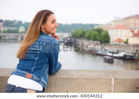 happy young woman enjoying the view from a bridge - stock photo