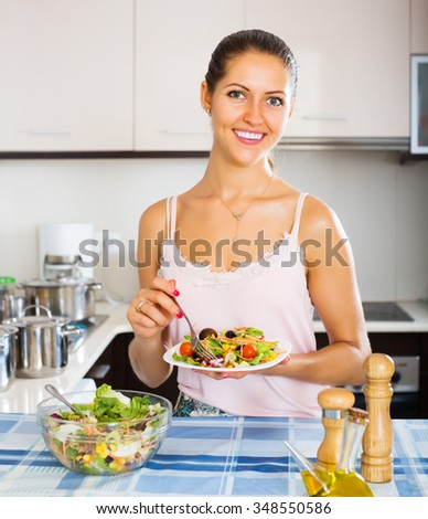 Happy young woman enjoying vegetable salad and smiling