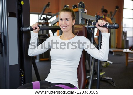 Happy young woman exercising on a shoulder press in fitness center - stock photo