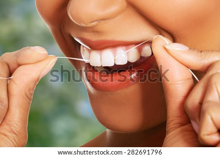Happy young woman flossing teeth.
