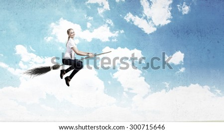 Happy young woman flying in sky on broom
