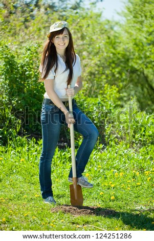 Happy young  woman gardening with spade in garden - stock photo