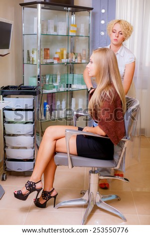Happy young woman getting her hair set by beautician after the new haircut - stock photo
