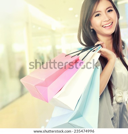 Happy young woman going shopping in the mall - stock photo