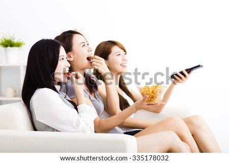 happy young woman group  eating snacks and watching the tv - stock photo