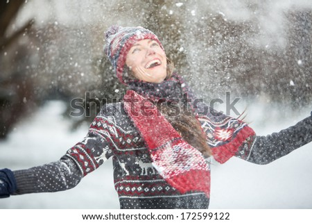 Happy young woman having fun on a snowy winter day outdoors - stock photo