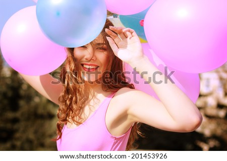 Happy young woman having fun with big colorful balloons - stock photo