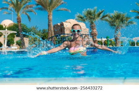 Happy young woman having fun with water splashes in pool - stock photo
