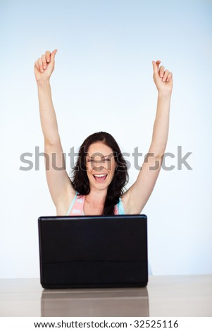 Happy young woman having success with laptop at home