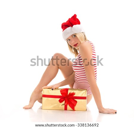 Happy young woman hold red Christmas wrapped gift present smiling sitting isolated on a white background