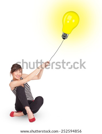 Happy young woman holding a light bulb balloon - stock photo