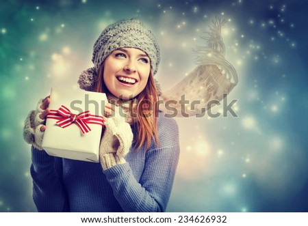 Happy young woman holding a present box in snowy night - stock photo