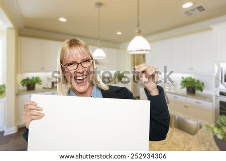 Happy Young Woman Holding Blank Sign and Keys Inside Beautiful Custom Kitchen.