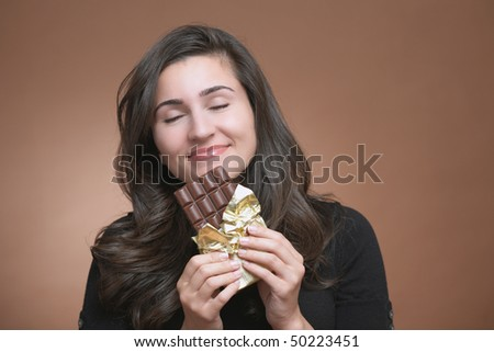 Happy young woman holding chocolate bar with copyspace - stock photo
