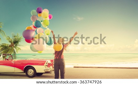 Happy young woman holding colorful balloons with floating, concept of journey honeymoon in summer on tropical beach blue sky - vintage color tone - stock photo