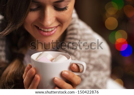 Happy young woman holding cup of hot chocolate with marshmallow