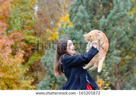 Happy young woman holding her red cat in park on autumn day - stock photo