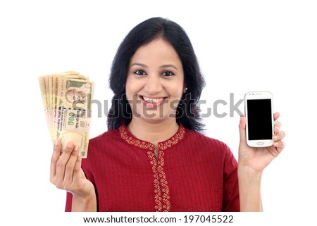 Happy young woman holding Indian currency and mobile phone - stock photo