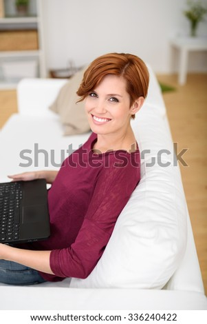 Happy Young Woman Holding Laptop Computer While Relaxing at the While Couch in the Living Room and Smiling at the Camera. - stock photo