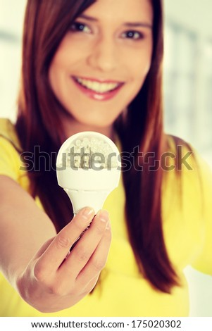 Happy young woman holding led bulb - stock photo