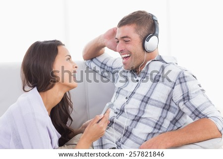 Happy young woman holding mobile phone while man listening music through headphone at home - stock photo