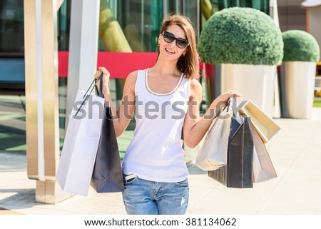 Happy Young Woman Holding Shopping Bags - stock photo