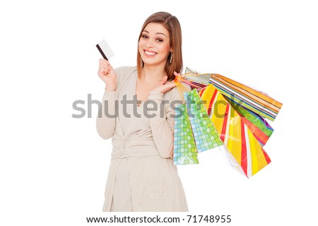 happy young woman holding shopping bags and showing credit card