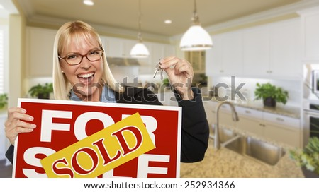 Happy Young Woman Holding Sold For Sale Real Estate Sign and Keys Inside Beautiful Custom Kitchen. - stock photo